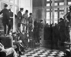 Spectators stand upon couches, tables and chairs to get even a glimpse of the Versailles Treaty being signed, 1919