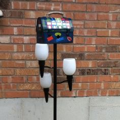 Painted lunchbox bird house perched on my repurposed 3 feeding light.