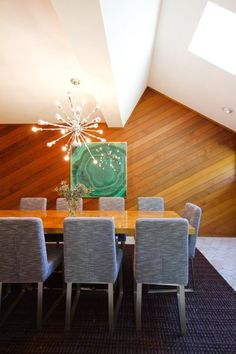 A Modern, Eclectic Retreat in the Woods — Professional Project. Diagonal slatted wood wall. Framed emerald color malachite scarf as art. Soft back dining room chairs. Hexagonal tile floor. Sputnik chandelier light.