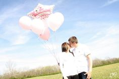Hold a balloon that says its a girl or just a pink balloon