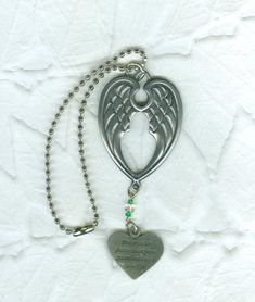 """This pewter ornament has a pair of angel wings topping a heart that reads: """"Never drive faster than your guardian angel can fly."""" It is suspended from a   three and one-half inch chain."""