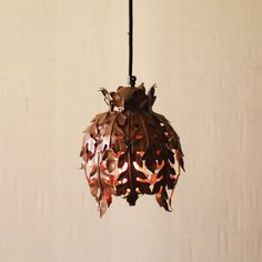 This striking pendant lamp layers warmth and naturalism hanging above your table or entryway. Rusty-hued metal is hammered into oak leaves, which we recommend nestling around a central chic Edison bulb.