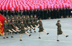 En esta foto difundida por la Agencia de Noticias Xinhua de China, las mujeres soldados marchan a través de la Plaza Kim Il Sung en Pyongyang, Corea del Norte, mientras que los ciudadanos sostienen paquetes de colores para formar una gran pantalla el martes 9 de septiembre de 2008.