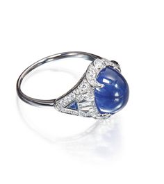 Platinum, Sapphire and Diamond Ring Centering a cabochon sapphire weighing approximately 6.25 carats, framed by round diamonds, accented by baguette diamonds, further set with two triangle-shaped sapphires