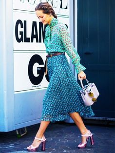 A patterned blouse is paired with a midi skirt, thin belt, mini bucket bag, and sparkly platforms