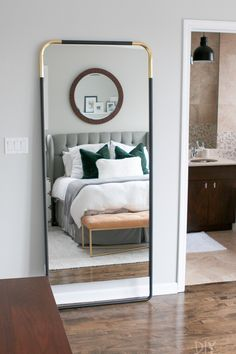A black and brass mirror that is secured to the wall using furniture straps.