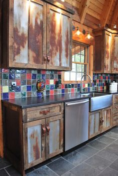 Cabin Kitchen. These cabinets were made from barn wood and rusted metal roofing. (--resourceful, rustic, primitive), slate floor, black counters (you pick the material used). Gallery lights above each cabinet lights up the dark interior of the kitchen & also helps to see what's inside each cabinet. Rustic tile backsplash can compliment artsy but functional pottery used/displayed.