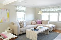 Gorgeous living room features tan colored walls framing windows dressed in white and blue zebra print roman shades over a modern linen chaise sectional topped with neutral patterned pillows and a lavender accent pillow.