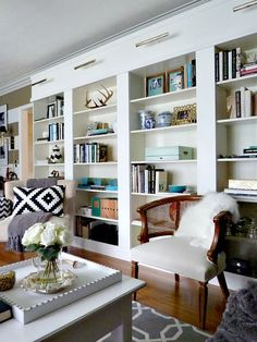 DIY Library Wall for Less Than $600- bhg.com 4 ikea 'billy' bookshelves, wood boards to trim out, brass picture lights (on remote, no less). i really would love to do this in our living room/office!