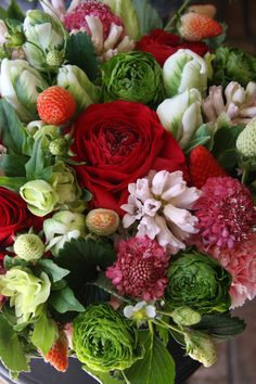 ranunculus,tulip,hyacinth,helleborus and strawberry in a gorgeous tight bouquet.