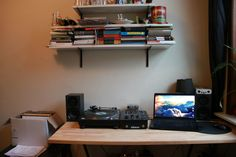 When living in a small space, sometimes you have to combine work and recreation areas. This desk was a solid choice because it's large enough to hold his laptop and dj equipment. To clean things up, we'd like to see him replace the cardboard box with a proper record crate.