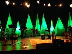 Create inexpensive pyramid shaped trees using plywood and vellum paper. Use stage lighting to create varying color effects. | Church Stage Design Ideas