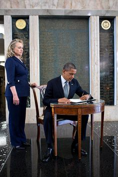 President Barack Obama signs a condolence book in memory of Chris Stevens. Secretary of State Hillary Rodham Clinton stands at left.