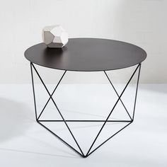 "LA-based designer Eric Trine ""designs by making, rather than drawing."" Each project begins in his studio with his hands and tools. The idea for these tables was born on one of his many trips to a metal supplier where he saw a disc of salvaged sheet steel. He welded the geometric steel base and powder-coated it so it can live indoors or out. We love it as a display spot for terrariums, books or flea market finds."