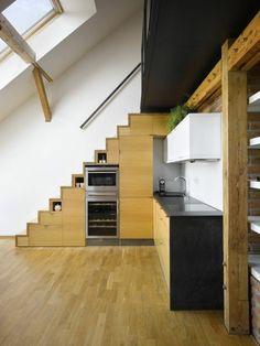 Maligne, la petite cuisine de cet appartement de deux niveaux sous combles s'intègre sous l'escalier et n'occupe qu'un seul mur.