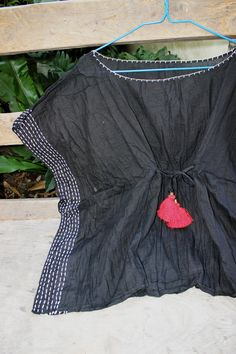 This loose fit, wide-boat neckline, extended sleeves made of Thai cotton which is very soft and light. To make it unique with hand-thread embroidery along the side-lines and neckline.  This piece is very comfortable to wear and easy to care for. If you like, no need to iron. Just twist to make crinkle and keep it in your closet. Fits great for L-XL Wide-boat neckline Extended sleeves Drawstrings at front to make it tighten at bustline, decorated with colorful silky tufts. Eleastic smock at…