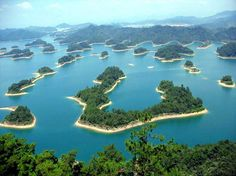 Qiandao Lake, Zhejiang  Thousand Islets Lake, or Qiandao Lake, is a beautiful man-made lake dotted with 1,078 islands of various sizes. The lake was formed after the construction of the Xin'an River hydroelectric station.   You may not know that there are two 2,000-year-old villages lying underneath the lake, which are perhaps more interesting and worthy of a visit than the lake itself. http://www.chinatraveltourismnews.com/2015/04/7-day-classic-tour-route-in-zhejiang.html