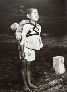 A Japanese boy standing at attention after having brought his dead younger brother to a cremation pyre in Nagasaki, 1945. [[MORE]] Source: Historical Photos