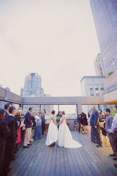 Let the wedding ceremony begin - on a hotel rooftop, no less! These brides have it all! {Kristin La Voie Photography}