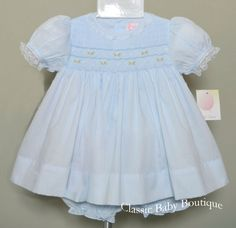 What an absolutely adorable dress from Petit Ami! Light blue smocked bodice dress with pink flower embroidery, delicate lace trim on the neck, bonnet and puff sleeve cuffs, buttons in the back, elasti