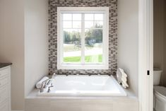 Bathtub with gray tile and gray accent wall. Corner Bathtub, Relax, Accent Wall, Grey Accent Wall, Tub Surround, Wall, Residential, Grey Tiles