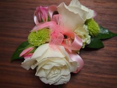 One of a kind prom corsage with pin cushion mums, white roses, rhinestones, pink ribbons, greens and matching boutonnière. www.urbanelementsinteriorspace.com  Portland, OR
