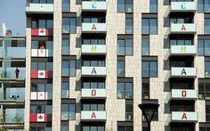 Members of the Canadian Olympic team stand on their balconies at the Canadian Olympic housing complex in the Olympic village on July 24, 2012, three days before the start of the London 2012 Olympic Games. (AFP/Getty Images)