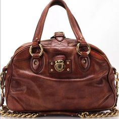 Marc Jacobs leather satchel with shoulder strap Leather satchel with a buckle & zip top closure.  There is an accent lock on the front and a removable chain strap. Beautiful Cognac Brown, The hardware is in rich gold. The leather is aged with wear which adds character: where the ring holds the chain strap is very worn. Small Ink stain on interior lining. This bag is from the full Collection line and not the cheaper MBMJ label. Trade value higher and the bundle deal not included. Marc Jacobs…