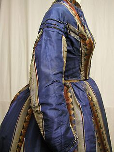 1860's dress with two bodices from a museum de-accession. Fabric is a silk stripe of blue, silver and brown. First bodice has short sleeves (W 22 B 31) and has brown cotton lining. Second bodice has long sleeves (W 24 B 33). Black braid trim with jet beads. Skirt (W 24 L 36, 170 inches at hem) is fully lined with brown cotton.
