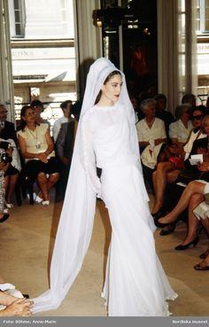 Modevisning. Modell i vit långklänning och vit slöja. Från Chanel.