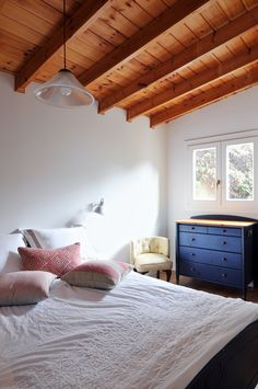 A white bedroom with a slated wooden ceiling. Designed by Liat Hadas, Architecture & Design.