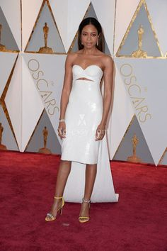 Naomi Harris in a white sequin strapless sweetheart cutout bodice knee length cocktail prom dress with floor length wrap Oscars at 2017 Red Carpet in Hollywood.