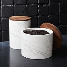 Upgrade your storage style with Ross Cassidy's refined take on humble kitchen canisters. Handcrafted from marble, oversized/low silhouette is topped with a warm acacia wood lid that gracefully conceals whatever's inside.