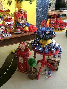 Decoração da mesa do bolo com tema patrulha canina: com objetos decorativos, suporte de doces porcelanas vermelhos e amarelos ,bonecos do tema em feltro, bolo fake forrado em tecido , caixas decorativas forradas em tecido e vasinhos. Arranjo de flores opcional
