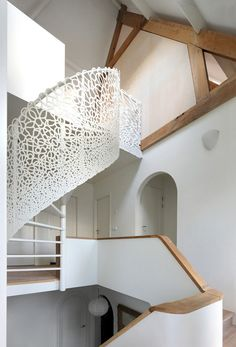 A seaside house gets a modern renovation including a spiraling laser-cut lattice staircase that winds up toward the sky, reminiscent of breaking waves.
