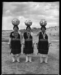 """""""Zuni Indian Pueblo women, balancing decorated pottery pots on their head during the Gallup Ceremonials. August 1939"""""""