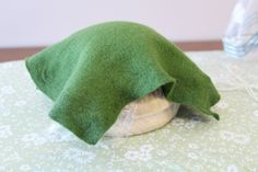 Hat: Wool felt is soaked in soapy water to allow the fibers to stretch.  Then, using the steam from the iron (and arm muscles), wool is stretched until it fits tightly over the form.