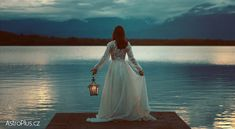 Photo about Woman waiting on a lake pier with lantern . Surreal and romantic. Image of light, romantic, manipulation - 72553799