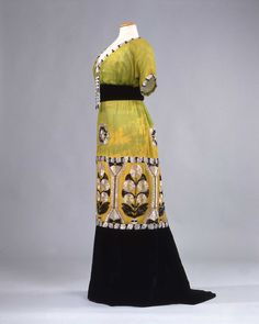 1913 evening dress in green and yellow chiffon with belt and big flounce in black velvet, embroidered with glass beads and straws in stylised flower motifs; Sartoria A La Ville de Lyon Raphael Goudstikker,...