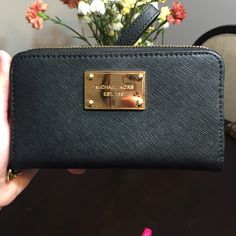 Michael Kors Wristlet/Wallet Black and gold. In great condition, only has a minor scuff on back (2nd photo). For cash and cards, can also fit an iPhone 5 in middle. Authentic. Michael Kors Bags Clutches & Wristlets