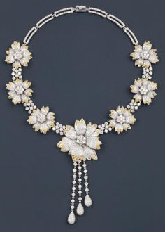 Collier articulé en or gris entièrement serti de diamants, orné de sept motifs «Fleur» sertis de diamants blancs et diamants jaunes naturels. Se retient au centre trois pampilles serties de diamants. Poids 125,1 g