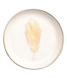 Weiß/Feder. Kleiner Porzellanteller mit goldfarbenem Rand und aufgedrucktem Federmotiv. Durchmesser 12,5 cm.