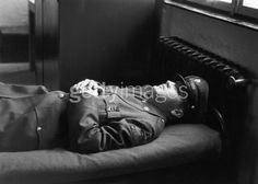 10th January 1958: Portrait of American rock singer Elvis Presley (1935 - 1977), wearing a military uniform, lying on an army cot with his hands folded across his chest.