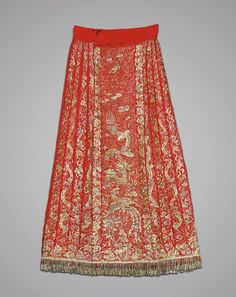 China, elaborately embroidered, wedding silk skirt; the front and verso with design of couched dragon and phoenix in gilt metal thread, flanked by rows of billowing clouds, on bright red ground; with twisted metal thread fringe