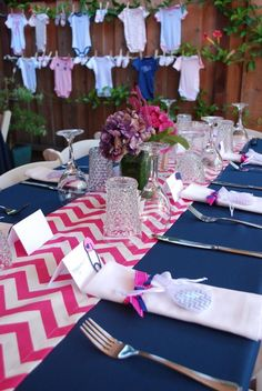 Pink and Navy Baby Shower Ideas - love this wall of onesies! Clothes are cute décor in a nursery too.