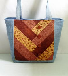 This large quilted denim blue jean and rust patchwork tote bag, shoulder bag, handbag or purse was constructed from upcycled recycled denim blue jeans and a variety of rust repurposed cotton fabric. This bag is spacious and durable, a perfect size to comfortably carry your daily must have items, magazines, books and miscellaneous items. Fill it up with your beach, school or work must have items. First....The Purse Dimensions: Bag Top Width (side seam to side seam) - 17 inches Bag Bottom…