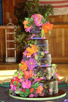 La joie de vivre! A fanciful and fabulous New Orleans inspired chocolate rolled fondant wedding cake. All of the playful yet elegant nuances of the French influence are captured here from the elaborate colorful brush embroidery to the intensely colored sugar roses, parrot tulips, fruits and berries.