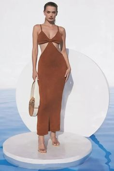 The Cult Gaia Serita is a cutout woven knit maxi dress. Thoughtful cutouts shape your figure, highlighting the small of your waist. A bra silhouette with a bare all open back. Pair with the Banu Bag and bare feet and you're ready for a night of dancing on the beach. This dress is worth all the Instagram hype! | Designer Dress | Knit Maxi Dress | Cutout Maxi Dress | Resort Dress | Resort Outfit | Wedding Guest Dress | Sexy Maxi Dress | Designer Summer Outfit | South Beach Dress | Cruise Outift | Cruise Dress, Cruise Outfits, Summer Outfits, Beach Dresses, Sexy Dresses, Summer Dresses, Wedding Rehearsal Dress, Brunch Dress, Resort Wear For Women