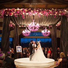 The traditional Jewish ceremony was held at dusk beneath a huppah draped in shimmery purple fabric. A striking circular stage mirrored the modern in-the-round seating arrangement and elevated the couple so guests could see.