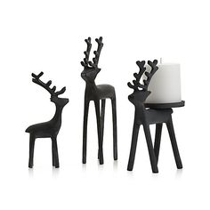 Rustic reindeer hoists a single pillar candle on its back, lighting the way to a festive holiday setting.